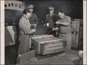 Crates of artwork are opened up under Army supervision.