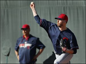 Cleveland Indians pitcher John Axford throws as manager Terry Francona looks on during spring training in Goodyear, Ariz. Axford is expected to replace Chris Perez as the Tribe's closer.