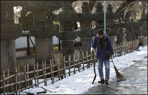 A worker walks away after shoveling snow off a court yard Sunday at a temple in Tokyo.