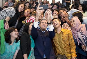 John Kerry takes a selfie with students before his speech Sunday in Jakarta, Indonesia. He said despite many looming disasters related to future climate change, there's still time to act and tackle the problem.