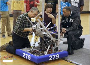 Mentor Skip Mozena, left, of Dana Holding Corp., repairs a robot that picks up and kicks a ball while Joe Neyhart, a senior at Toledo Technology Academy, explains the process to Romules Durant, superintendent of Toledo Public Schools.