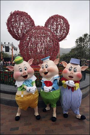 Disney's Three Little Pigs pose in front of a cherry blossom Mickey Mouse at Hong Kong Disneyland.