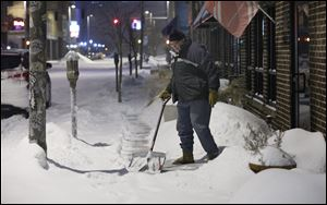 Downtown Toledo resident and business owner Paul Sullivan gets an early start shoveling the sidewalk in front of his architecture office on South St. Clair Street.