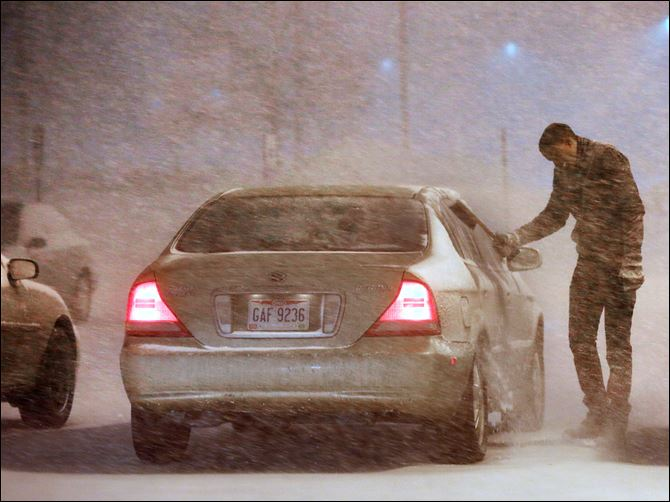 n3snow-1 Owens Community College student Usen Ekpek shields his face from blinding snow Monday as he brushes off his car at the school's Perrysburg Township parking lot.
