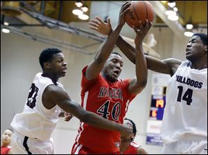 Rogers' Fadil Robinson (40) pulls in a rebound against Scott's Trey Brown (23) and Percy Bogan (14).
