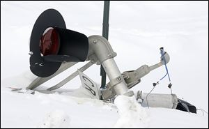 A railroad crossing signal is destroyed near  the derailment site. No one was injured in the incident.