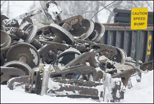 The wheels of railroad cars are piled up as workers clear a train derailment in Tontogony, Ohio. Debris near the track could remain for months.
