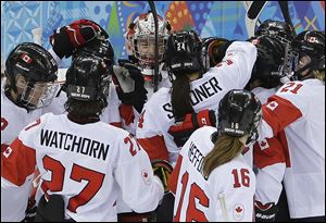 Goalkeeper Shannon Szabados of Canada is surrounded by teammates after Canada's 3-1 win over Switzerland in a 2014 Winter Olympics women's semifinal game at Shayba Arena, Monday in Sochi, Russia.