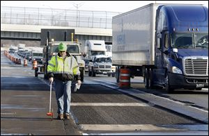 Ohio Department of Transportation official Dave Kanavel prepares to fix potholes on I-75 north of the I-475 split in Toledo. Parts of I-75 and I-475 will be closed today so crews can repair potholes.