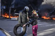 People-speak-near-a-barricade-on-fire-during-clashes