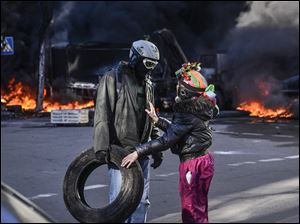 People speak near a barricade on fire during clashes between anti-government protesters and Interior Ministry members in Kiev.