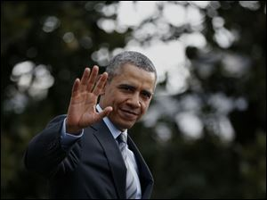 President Barack Obama waves to reporters as he walks on the South Lawn of the White House in Washington today.