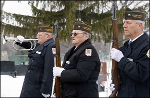 Joe Soinski  plays the bugle while Rob Greenlese and Larry Hall, right,  fellow members of the Lucas County Veterans Burial Corps, stand at attention during the funeral of Navy veteran Joseph John Patay on Wednesday at Mount Carmel Cemetery in Toledo.