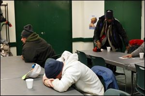 Homeless men gather in the lounge of St. Paul's Community Center Tuesday morning.