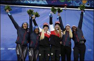 From left to right, silver medal winners from the United States Elana Meyers and Lauryn Williams, gold medal winners from Canada Kaillie Humphries and Heather Moyse, and bronze medal winners from the United States Jamie Greubel and Aja Evans pose during the flower ceremony for the women's bobsled competition.