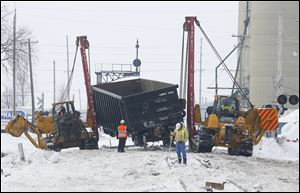 Workers clear the wreckage from a train derailment in Tontogony, Ohio. Nineteen cars of a CSX train derailed shortly after 9:30 p.m. Monday on the Wood County village's Main Street. Cleanup was ongoing throughout Tuesday.