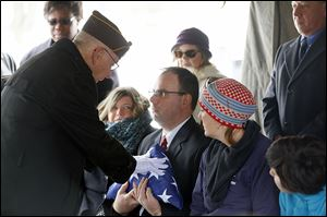 Cmdr. Terry Mohler of the Lucas County Veterans Burial Corps gives the flag that had been on the casket of Joseph John Patay to his son Joseph, Jr., during the funeral at Mount Carmel Cemetery.