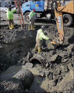 City employees fix a water-main break on Broadway between South Hawley and Stebbins streets in South Toledo. It was the city's second major water-main break in a week, and a city official said he had no idea when Broadway — which sustained extensive buckling and heaving — might reopen.