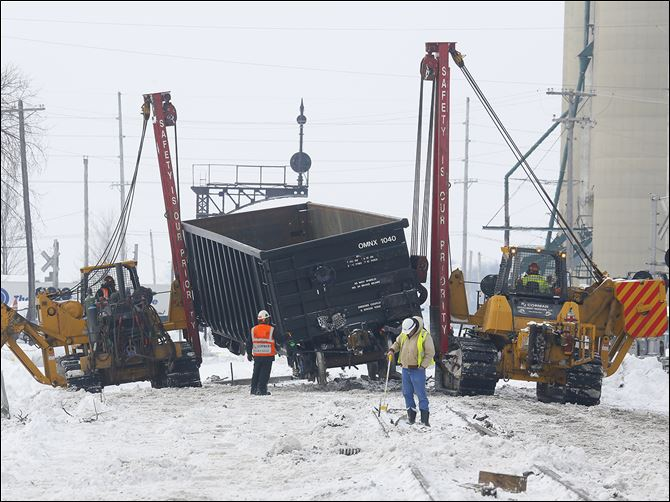 CTY trainderail19p Workers clear the wreckage from a train derailment in Tontogony, Ohio. Nineteen cars of a CSX train derailed shortly after 9:30 p.m. Monday on the Wood County village's Main Street. Cleanup was ongoing throughout Tuesday.