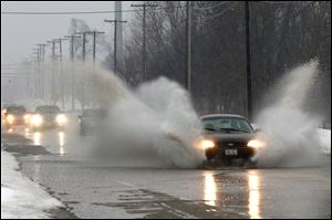 Plumes erupt from cars passing through water on Sylvania Avenue near Centennial Road in Sylvania Township, the result of melting snow and rainfall.
