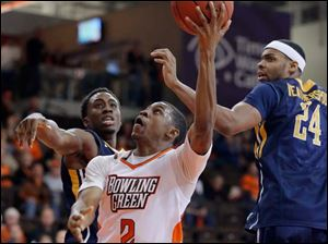 BGSU guard Anthony Henderson (2) goes to the basket against Toledo defenders Justin Drummond (4) and J.D. Weatherspoon (24).