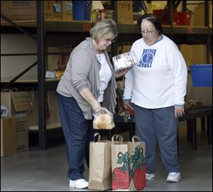 Amy Aschemeier, left, puts food items into a bag for Sue Fields at the Perrysburg Christians United food pantry.