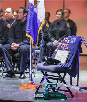 An empty chair marks the absence of firefighter James Dickman during a graduation ceremony for the Toledo Fire Department at the University of Toledo's Doermann Theatre. Mr. Dickman died in the line of duty on Jan. 26.
