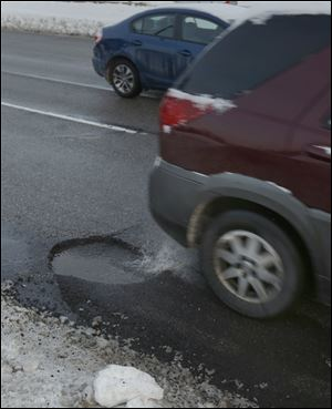 Potholes litter all three lanes of Anthony Wayne Trail in Toledo. The city says it has filled 12,664 potholes since the first of the year. In the meantime, motorists must weigh the cost of filing a claim compared to paying costs out of pocket.