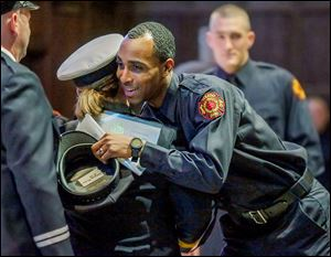 Pvt. Antwoine Mister hugs Battalion Chief Sally Glombowski after receiving his hat during a graduation ceremony for the Toledo Fire Department. Private Mister was among 47 new firefighters who graduated on Friday.