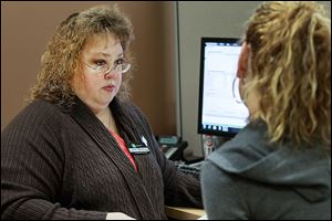 Lynn Bishop of Toledo, a tax specialist with H & R Block in Holland, helps a client prepare her taxes.