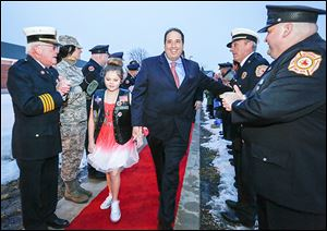 Uniformed personnel cheer Marlee Eckert, 10, as she and Dave Miramontes, her grandfather, walk the red carpet to Waterville Primary School's Winter Ball.