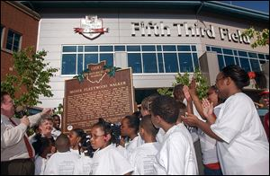 In 2003, Peter Ujvagi, left, then a state representative, was joined by schoolchildren as an Ohio Historical Marker was unveiled to honor Moses Fleetwood Walker in front of the Toledo Mud Hens' stadium, Fifth Third Field.