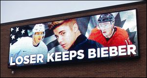 An electronic billboard displays pop star Justin Bieber, center, sandwiched by Chicago Blackhawks stars Patrick Kane, left, and Jonathan Toews outside the Skokie, Ill.