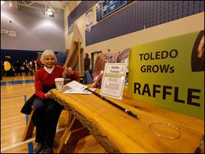 Elizabeth Harrington of Toledo sitting at Toledo Grows' rustic table with two chairs and two benches that was built by Toledo Grows.