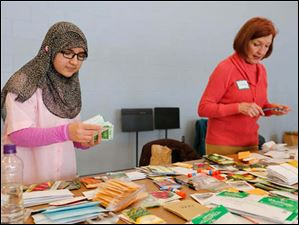 Woodward High School sophomore and Young Women of Excellence member Falak Naz, 15, left, sorts donated seeds while volunteer Nancy Grindulis gives donors tickets for the swap.