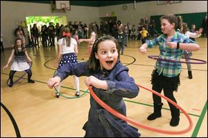 Eleanor Kelso, 9, center, laughs with a classmate as she almost drops her hula hoop during a dance party at Sylvan Elementary School in Sylvania. Enrollment runs from kindergarten to fifth grade.