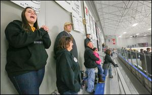 Kayleen Jurski, a senior at Perrysburg High School, and her parents, Jackie and Ron, cheer her brother Chris at a Perrysburg hockey game against Clay at the Monroe Sports Complex. Kayleen's surgery will force her to give up playing softball, but the team has requested she remain a captain.
