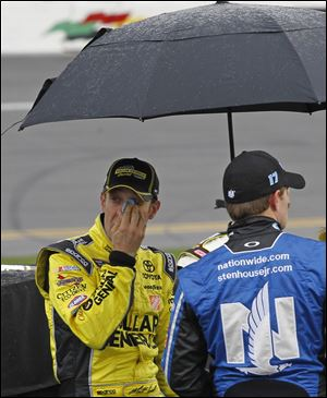 Matt Kenseth, left, looks out from under an umbrella as he stands near his car during a rain delay Sunday.