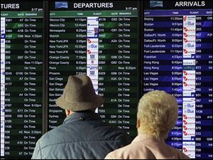 Passengers look at the arrivals and departures board at the international terminal at San Francisco International Airport. CheapAir.com advises being flexible to avoid the most popular travel days.