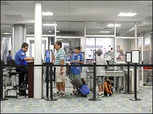 Passengers go through security at Toledo Express Airport. Need to add a line from the story to make second line, Passenger traffic in Toledo grew from 159,295 travelers in 2013 from 143,514 in 2012.
