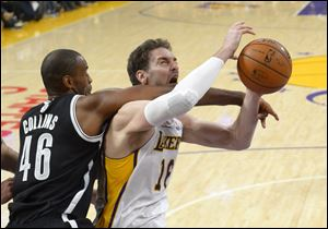 Brooklyn Nets center Jason Collins, left, fouls Los Angeles Lakers center Pau Gasol on Sunday in Los Angeles. The Nets won 108-102. Collins was signed to a 10-day contract Sunday, nearly 10 months after his announcement on April 29 in Sports Illustrated. He played 10 scoreless minutes with two rebounds and five fouls.