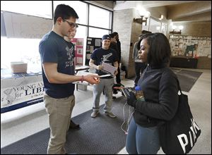 Ron Johns, 21, president of the University of Toledo chapter of the Young Americans for Liberty, hands a fake cigarette to fellow student Marshae Foy, 20, of Cleveland at UT's student union.