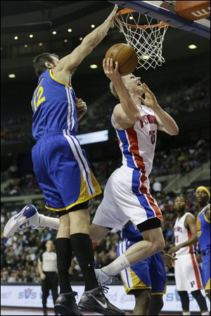 Detroit Pistons forward Kyle Singler (25) shoots while defended by Golden State Warriors center Andrew Bogut (12).