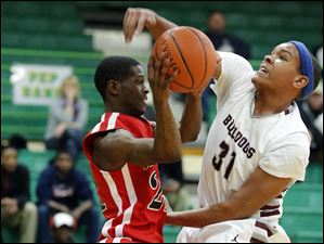 Rossford's Brian Burks (31) defends against Rogers' Omari Hicks (21) during a Division II boys sectional basketball game Tuesday, 02/25/14, in Oregon, Ohio. Rogers defeated Rossford 69-67 in overtime.
