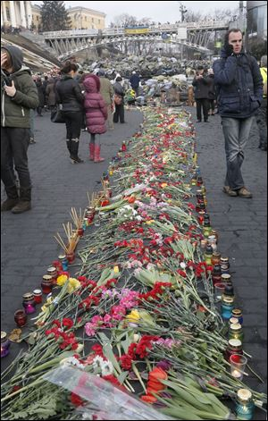 People lay down flowers on one of the streets leading to Independence Square, Kiev,  the epicenter of the country's recent unrest, on a mourning day,  Monday.