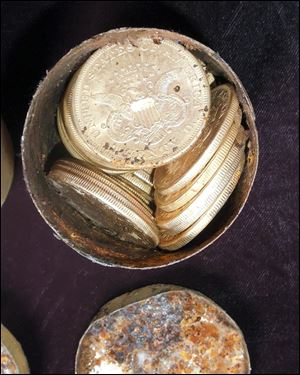 This image provided by the Saddle Ridge Hoard discoverers via Kagin's, Inc., shows one of the six decaying metal canisters filled with 1800s-era U.S. gold coins unearthed in California.