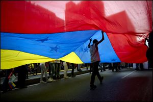 A youth walks under a large Venezuelan flag during a rally organized by workers of the National Telecommunications Company or CANTV to show support for the government.