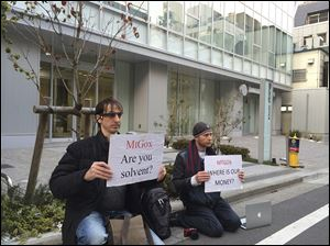 Bitcoin trader Kolin Burges, right, of London and an American counterpart hold signs during a sit-in in front of the office tower housing Mt. Gox in Tokyo. Reports say the major bitcoin exchange suffered catastrophic losses, handing the virtual currency a setback in its quest for legitimacy.