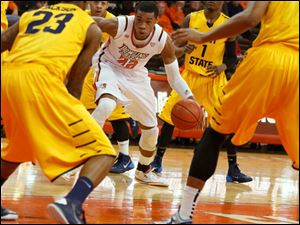 BGSU's Richaun Holmes is surrounded by Kent State defenders .
