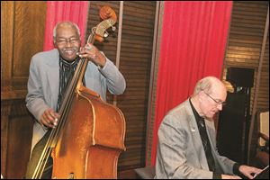 Clifford Murphy plays the bass at his 82nd birthday party at the Toledo Club.